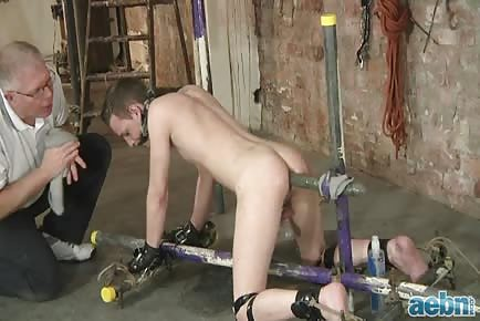 The master cuffs his slave and gives him some gigantic dildo punishment